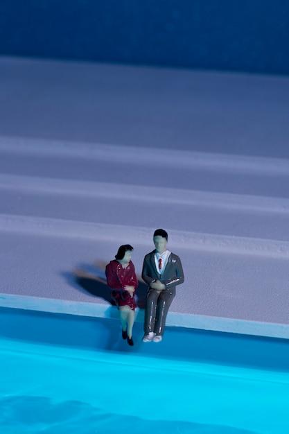 Puppen sitzen neben dem schwimmbad Kostenlose Fotos