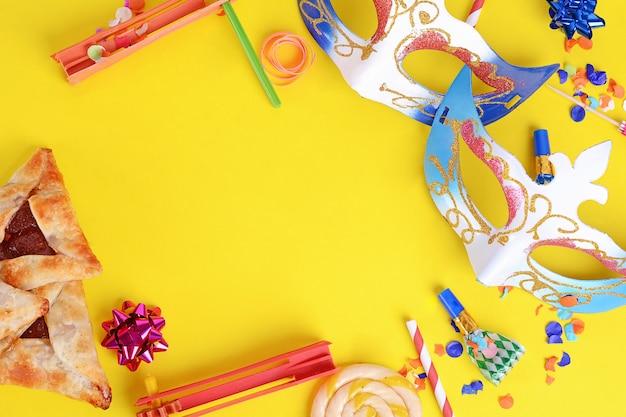 Purim-hintergrund mit karnevalsmaske, partykostüm und hamantaschen-keksen. Premium Fotos