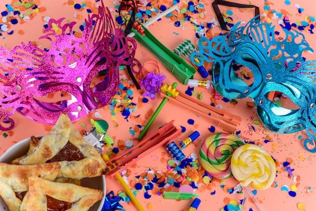 Purim mit karnevalsmaske, partykostüm und hamantasc Premium Fotos