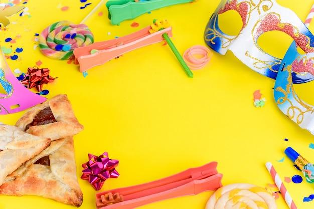 Purim mit karnevalsmaske, partykostüm und hamantaschen Premium Fotos