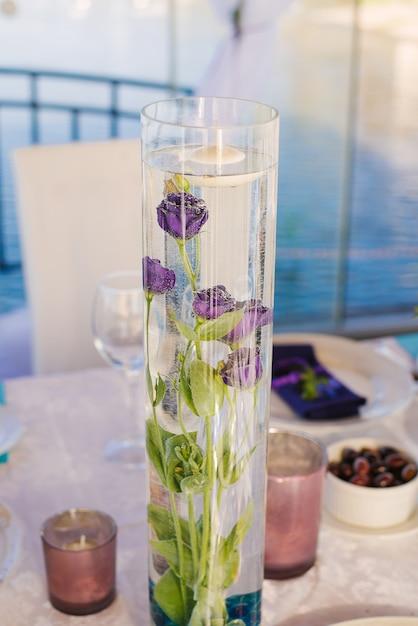 Purpurrote eustomablumen in einer glasvasenflasche auf einem festlichen bankett Premium Fotos