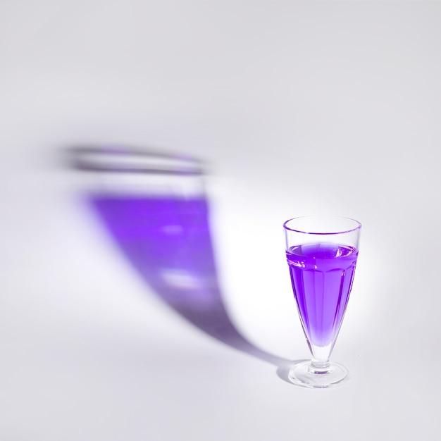 Purpurrote flüssigkeit im einzelnen glas mit schatten über weißem hintergrund Kostenlose Fotos