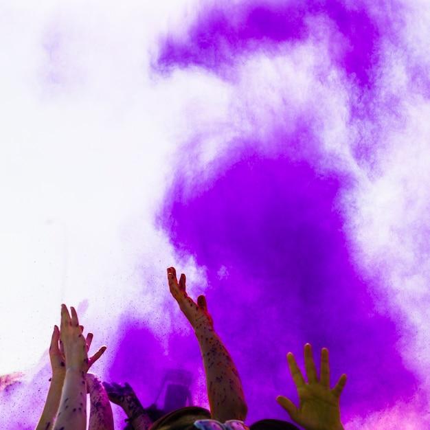Purpurrote holi farbe über den leuten, die ihr handtanzen anheben Kostenlose Fotos