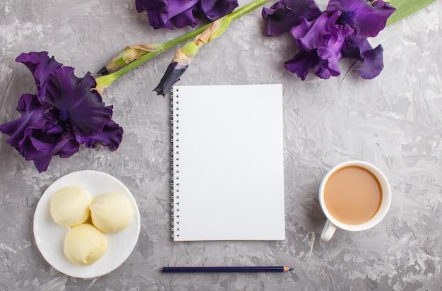 Purpurrote irisblumen und ein tasse kaffee mit eibisch und notizbuch auf grauem beton Premium Fotos