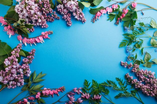 Purpurrote lila und blutende herzblumen auf blauem pastellhintergrund. Premium Fotos