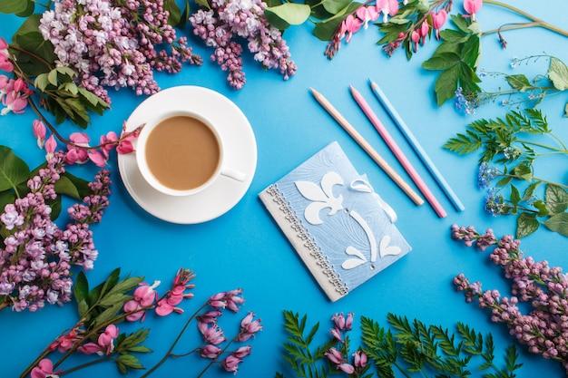 Purpurrote lila und blutende herzblumen und ein tasse kaffee mit notizbuch und farbigen bleistiften auf blauem pastellhintergrund Premium Fotos