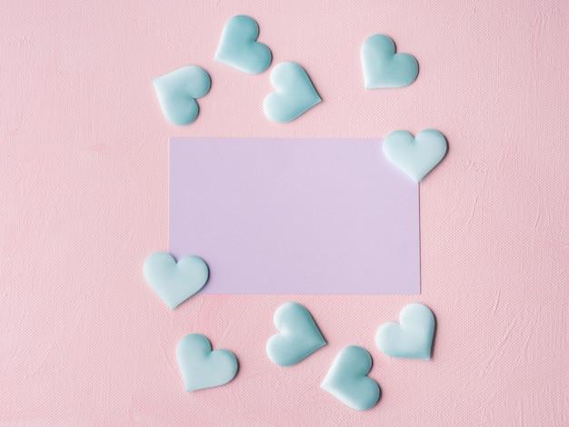 Purpurrote pastellkarte und herzen auf dem rosa gemasert Premium Fotos