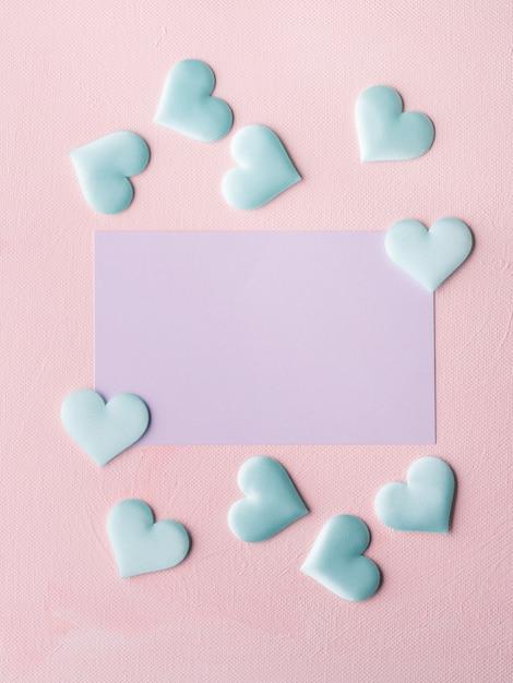 Purpurrote pastellkarte und herzen auf rosa strukturiertem hintergrund Premium Fotos