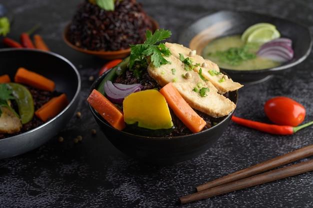 Purpurrote reisbeeren gekocht mit gegrillter hühnerbrust. kürbis, karotten und minze in einer schüssel, sauberes essen. Kostenlose Fotos