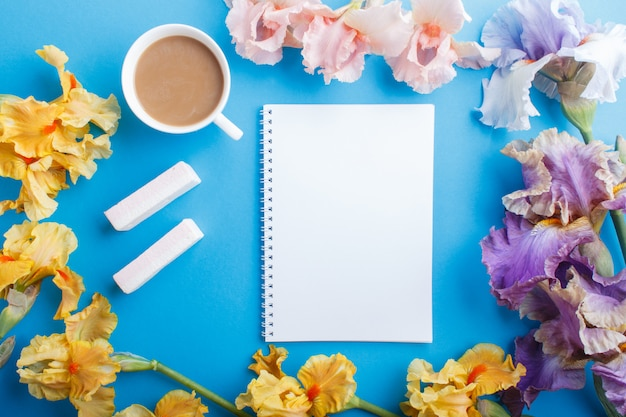Purpurrote, rosa, gelbe irisblumen und ein tasse kaffee mit notizbuch auf pastellblau. Premium Fotos