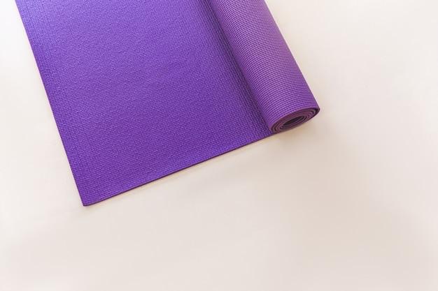 Purpurrote yogamatte, die auf dem hellen boden liegt Premium Fotos