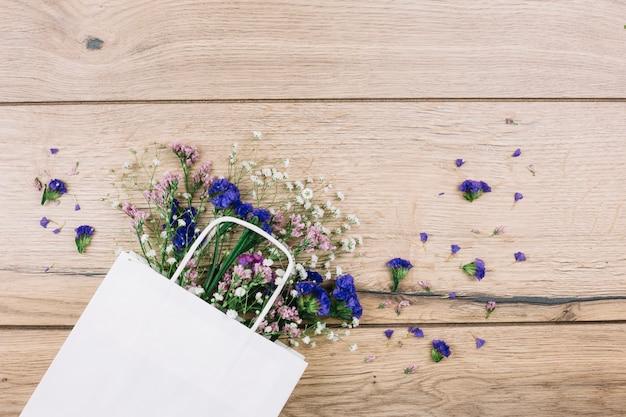 Purpurroter limonium und gypsophila blüht innerhalb der weißen einkaufstasche auf hölzernem schreibtisch Kostenlose Fotos