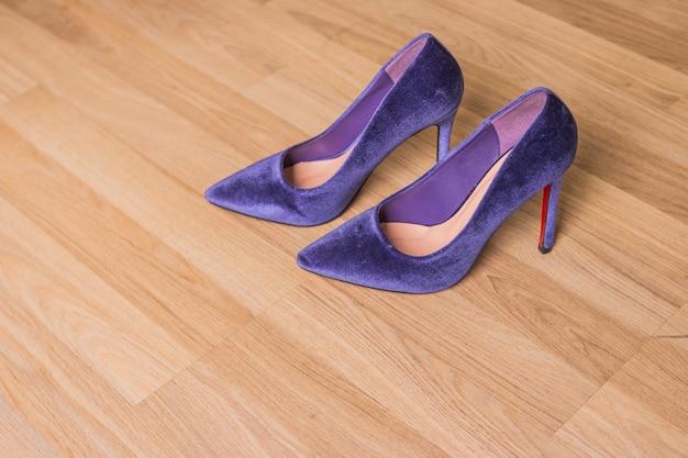 Purpurroter samt beschuht fersen auf holz. schöne mode eleganz und luxus high heel schuhe. trendy samtpumps für damen Premium Fotos