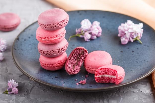 Purpurrotes und rosa macaron oder makronenkuchen auf blauer keramischer platte auf grauem beton. Premium Fotos