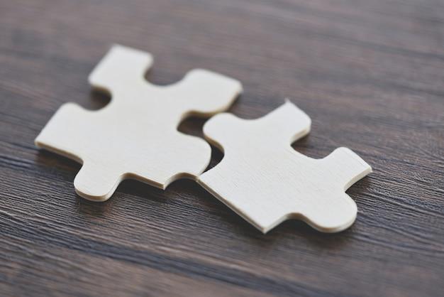 Puzzle auf hölzerner draufsicht - verbindung mit zwei puzzlestücken Premium Fotos