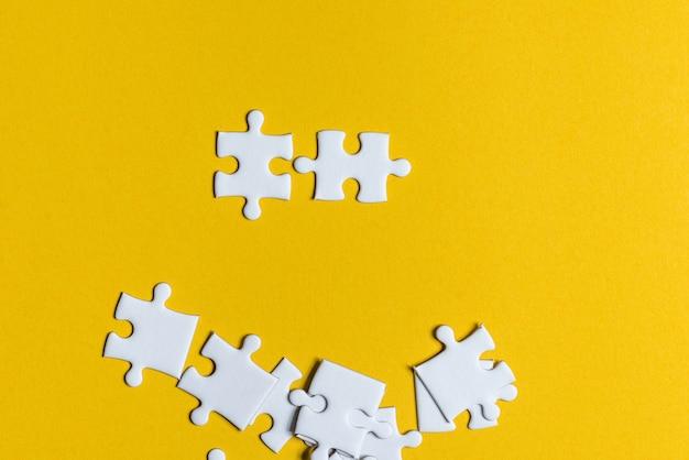Puzzlespiele platziert auf ein kreatives konzept des gelben hintergrundes mit kopienraum Premium Fotos