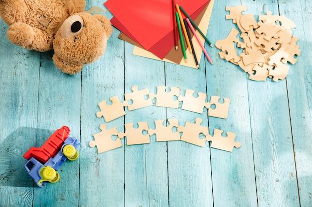 Puzzleteile, buntstifte, spielzeuglastwagen, teddybär und papier auf einem holztisch. konzept der kindheit und bildung. Kostenlose Fotos