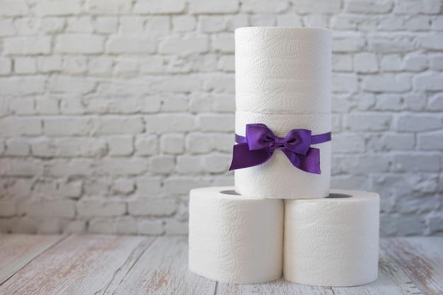 Pyramide aus weißen toilettenpapierrollen. rolle toilettenpapier mit einer lila schleife Premium Fotos