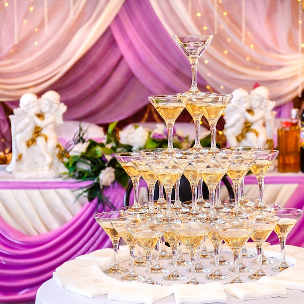 Pyramide von gläsern mit champagner im purpurroten hochzeitsinnenraum. Premium Fotos