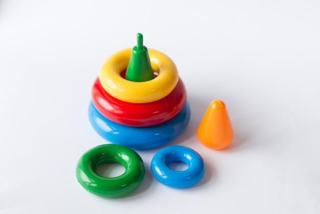 Pyramidenbau aus farbigen ringen mit einem clownkopf oben drauf. spielzeug für babys und kleinkinder, um spielerisch mechanische fähigkeiten und farben zu erlernen. studioaufnahme auf weiß. Premium Fotos