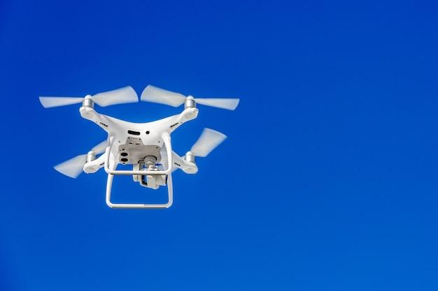 Quadcopter brummen mit der kamera gegen den blauen himmel Premium Fotos