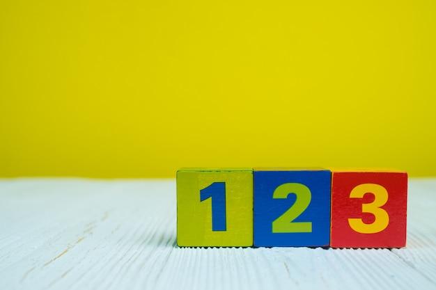 Quadratblockpuzzlespiel nr. 1 2 und 3 auf tabelle mit gelb Premium Fotos