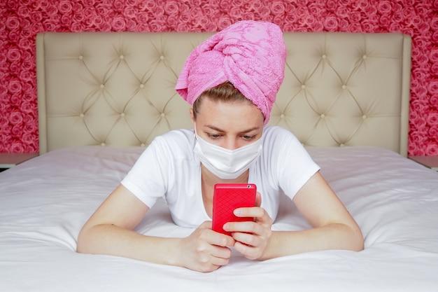 Quarantäne zu hause. ein junges kaukasisches blogger-mädchen in maske und einem handtuch auf dem kopf liegt mit einem telefon auf dem bett. fernkommunikation in messenger. Premium Fotos