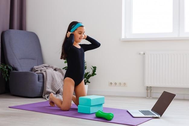 Quarantäne zu hause. kleines mädchen machen yoga während der selbstisolationsquarantäne Premium Fotos