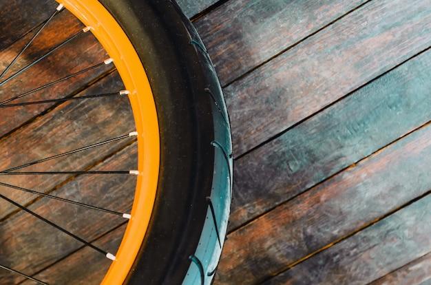 Rad eines stilvollen fahrrads mit einer orange felge und gummireifenabdeckung, hölzernem hintergrund. Premium Fotos