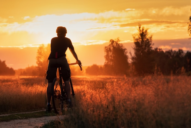 Radfahrer auf einem schotterrad steht in einem feld auf einem schönen sonnenunterganghintergrund. Premium Fotos