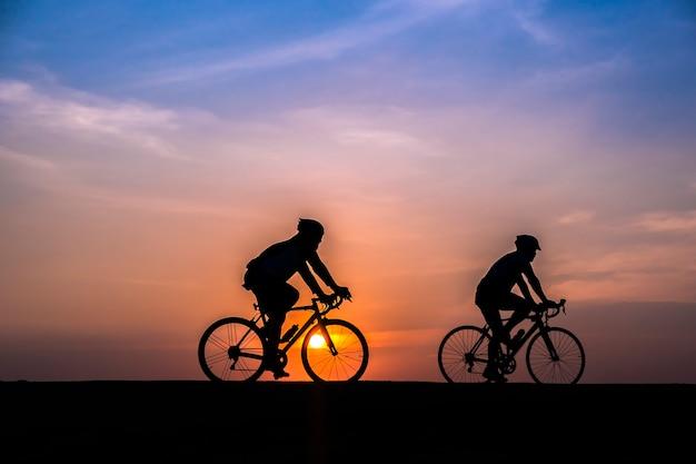 Radfahrer auf sonnenuntergang hintergrund Premium Fotos