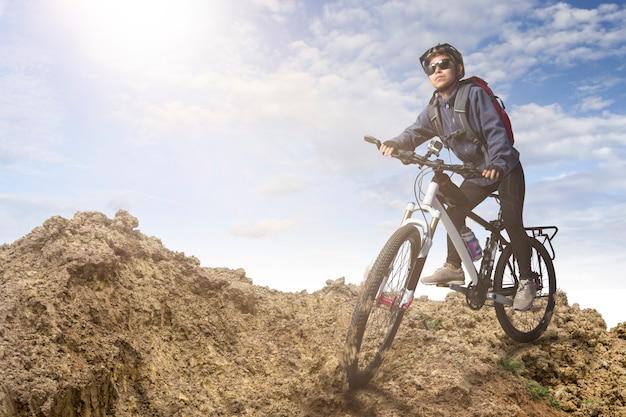 Radfahrer, der auf fahrrad in den bergen auf sonnenuntergang fährt Premium Fotos