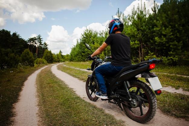 Radfahrer, der motorrad auf schotterweg mit sturzhelm reitet Kostenlose Fotos