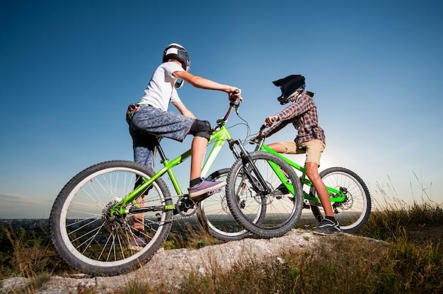 Radfahrer mit mountainbikes auf dem hügel unter blauem himmel Premium Fotos