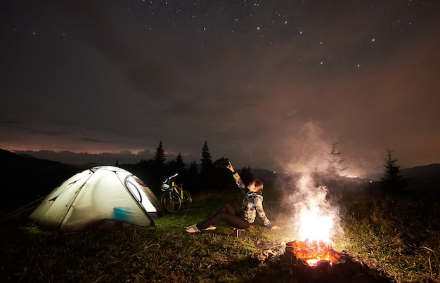 Radfahrerin in der nacht, die nahe brennendem lagerfeuer kampiert Premium Fotos