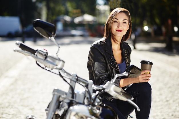 Radfahrermädchen in einer lederjacke auf einem motorrad Kostenlose Fotos