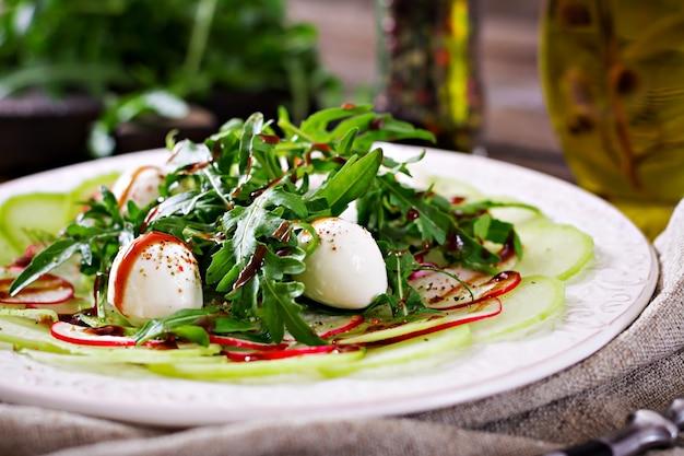 Radieschen-carpaccio mit rucola, mozzarella und balsamico-sauce. gesundes essen. daikon salat. Premium Fotos
