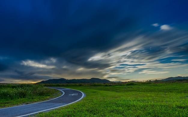 Radweg im park mit sturmwolken Premium Fotos