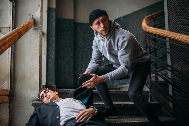Räuber tötet sein opfer und nimmt eine handtasche in den eingang. theif begeht einen raubangriff auf einen mann. verbrechenskonzept Premium Fotos