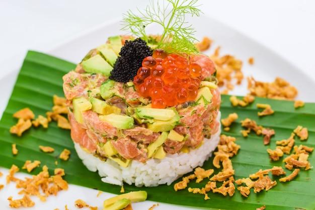 Räucherlachstatar mit avocado, reis und kaviar Premium Fotos