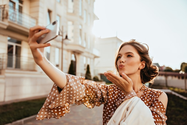 Raffinierte kaukasische junge frau, die telefon für selfie im herbsttag verwendet. außenaufnahme des glamourösen weiblichen modells in den braunen kleidern, die luftkuss senden. Kostenlose Fotos