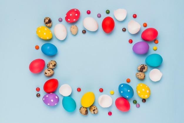 Rahmen aus ostereier und süßigkeiten auf dem tisch Kostenlose Fotos