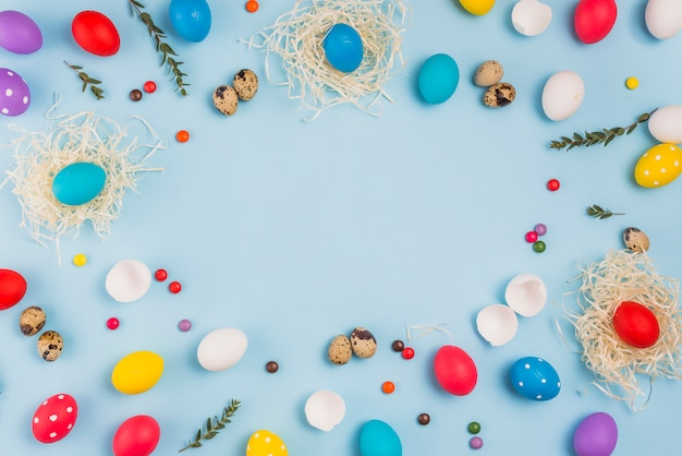 Rahmen aus ostereiern in nestern und süßigkeiten Kostenlose Fotos