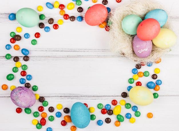 Rahmen aus ostereiern und kleinen süßigkeiten Kostenlose Fotos