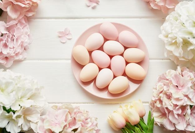 Rahmen aus rosa und beigen hortensienblüten, rosa eiern und gelben tulpen Premium Fotos