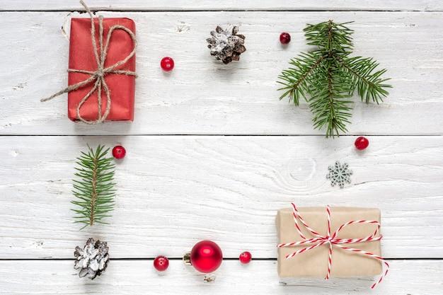 Rahmen aus weihnachtsgeschenk, tannenzapfen, tannenzweigen, roter kugel und beeren Premium Fotos