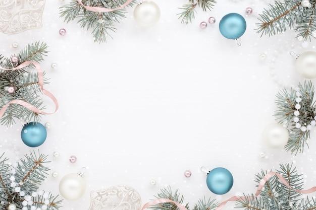 Rahmen mit blauen weihnachtsdekorationen und tannenbaum auf weißer oberfläche Premium Fotos