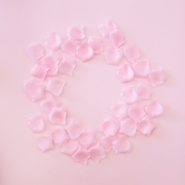 Rahmen mit rosa rosenblättern auf rosa hintergrund gemacht Kostenlose Fotos