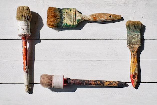 Rahmen von alten pinseln mit farbspuren auf weißem tisch Premium Fotos
