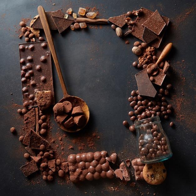 Rahmen von verschiedenen pralinen und kakaopulver auf einem dunklen hintergrund Premium Fotos